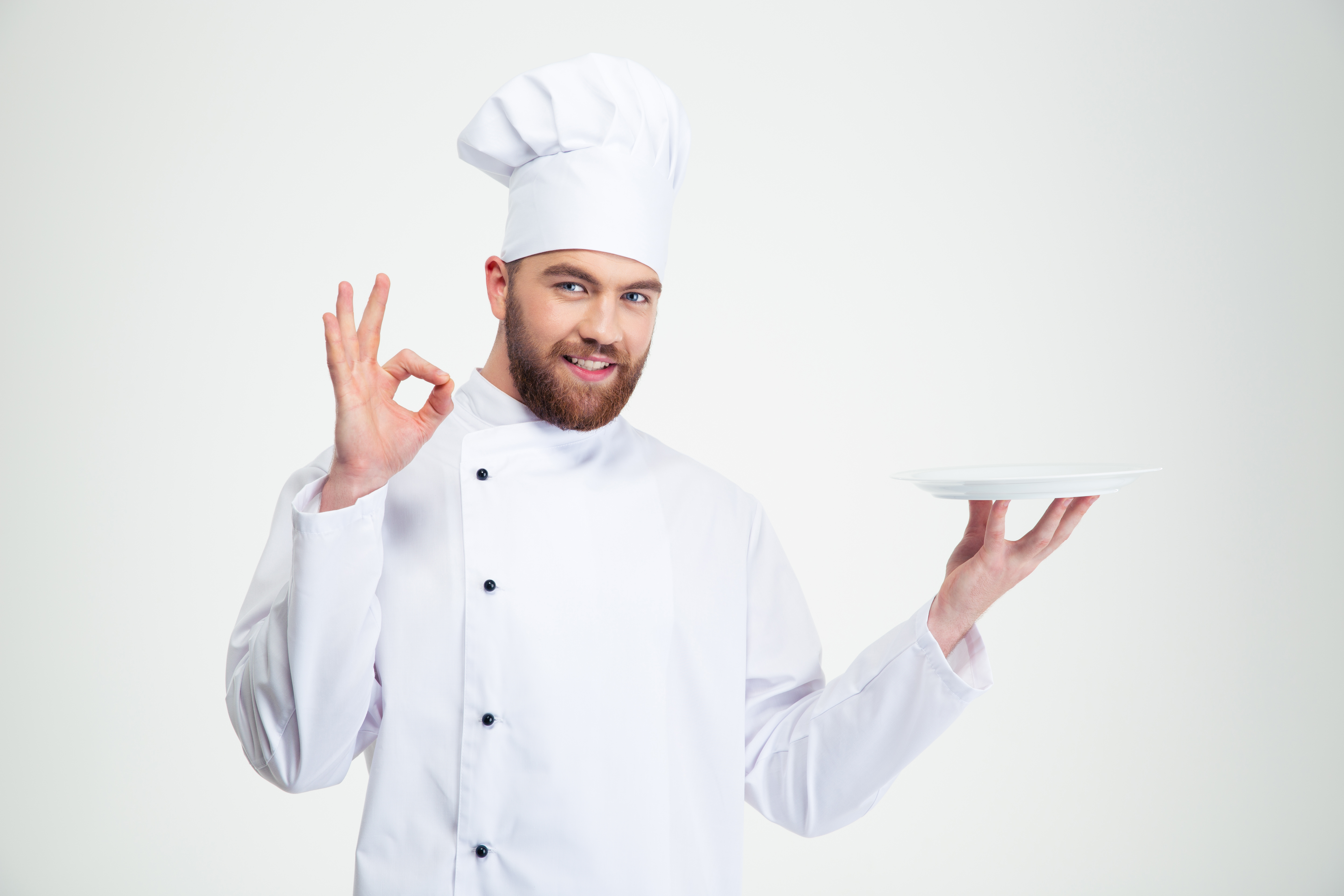 Portrait of a man chef showing ok sign and empty plate isolated on a w