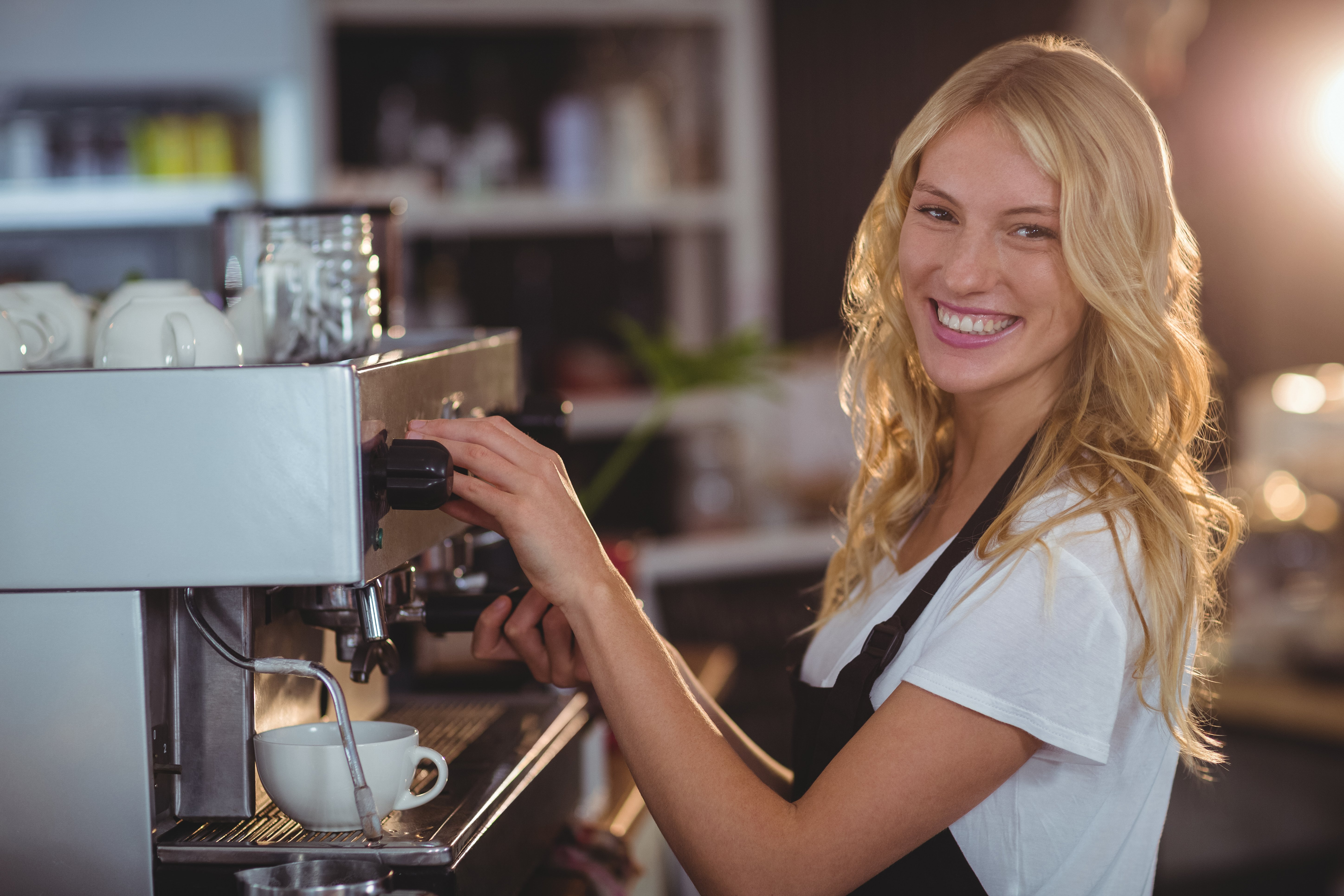 Portrait of smiling waitress making cup of coffee in cafe-1